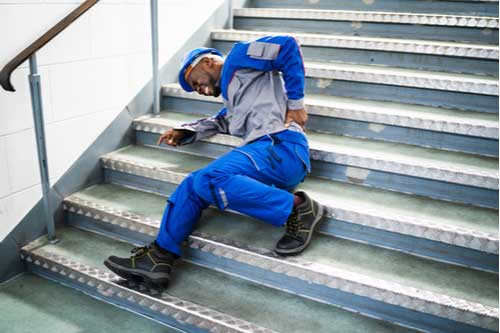 Man Lying On Staircase After Workplace Slip And Fall Accident