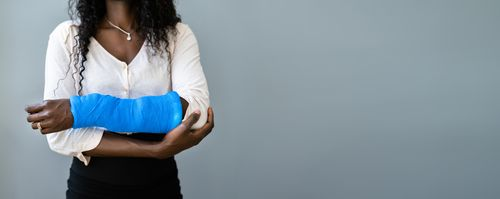 Female employee with injured arm concept of Fort Lauderdale workers' compensation lawyer
