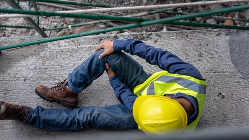 Injured construction worker holding knee concept of compensable work injuries in Orlando