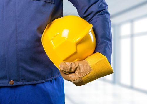 Construction workers holding helmet concept of workers' compensation disputes in Orlando
