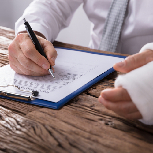 Image is of an injured employee filling paperwork to begin the workers' compensation claims process in Boca Raton