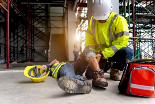 Injured employee on ground reporting a work injury in Boca Raton to supervisor
