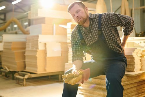 Man working with lumber with a back injury