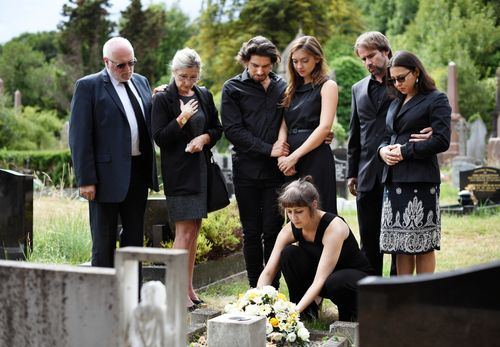 Family gathered around graveside of their loved one who suffered a fatal workplace injury