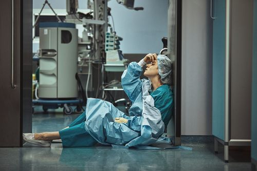 Healthcare worker on floor after sustaining hospital workplace injuries
