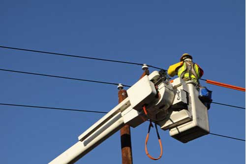 Lineman repairing cables, concept of utility worker injuries