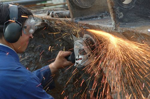Employee using grinder that is causing sparks and wearing protection to keep safe from hearing and vision loss