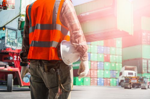 Worker looking at shipping container as its being lifted concept of falling/flyings objects at work