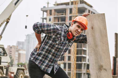 Construction worker with hurt back, concept of workers' comp in Tampa