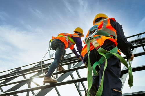 Two construction workers harnessed to keep from having a fall from heights